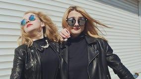 2 стильных маленькой девочки в кожаных куртках и солнечных очках на белой предпосылке показывают жест Перст вниз Справочная инфор акции видеоматериалы