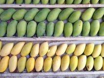 Стога желтых сладостной ароматности зрелых и зеленых манго приносить на деревянном стоге Стоковые Изображения