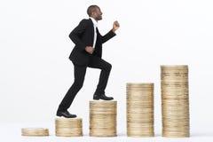 Стога монетки бизнесмена взбираясь стоковая фотография