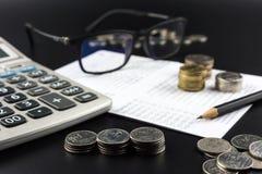 Стога монетки и и калькулятора на банке определяют дело Стоковые Фотографии RF