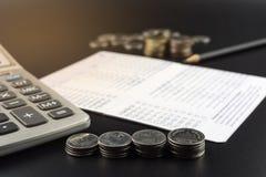 Стога монетки и и калькулятора на банке определяют дело Стоковое фото RF