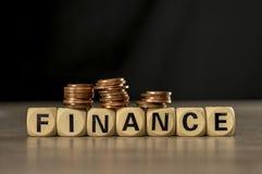 Стога монетки на письме преграждают собирать финансы слова стоковое фото