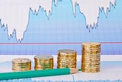 Стога монетки тенденции к повышению золотые, зеленый карандаш и финансовая диаграмма Стоковое Фото