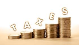 Стога монеток на белой предпосылке с налогами надписи стоковые фото