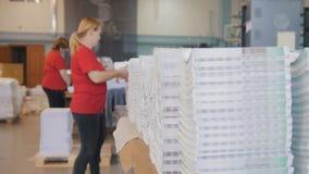 Стога напечатанного варианта перед видом работницы газеты в оформлении Стоковое Фото