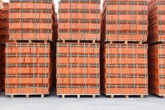 Стога нового, красного керамического кирпича штабелированного на деревянных паллетах стоковые фотографии rf