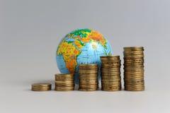 5 стогов монеток с глобусом Стоковая Фотография