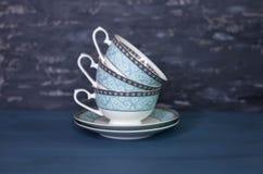 Стог античных чашек чая, изолированный на белизне Красивый фарфор стоковые фотографии rf