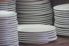 Стог белых чистых блюд помещенных на деревянной полке для того чтобы подготовить для шведского стола в утре сфокусируйте мягко Стоковое Изображение RF
