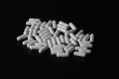Стог белых пилюлек медицины на черной предпосылке Стоковое фото RF