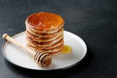 Стог блинчиков с лить медом на темной предпосылке концепция и завтрак украшения стоковые фото