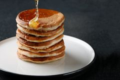 Стог блинчиков с лить медом на темной предпосылке ложка меда стоковые фото