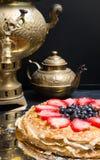 Стог больших блинчиков испечет в металлической пластине и чае от самовара на предпосылке Конец-вверх Стоковое Изображение