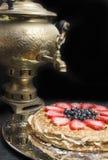 Стог больших блинчиков испечет от клубники, голубики и сконденсированного молока в металлической пластине и чая от самовара старо Стоковое фото RF