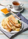 Стог блинчика заполнил с кусками и медом банана Стоковые Фото