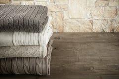 Стог вязать одевает на деревянном столе напротив каменистой стены Стоковая Фотография