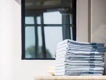 Стог голубых полотенец на палубе Окном Стоковая Фотография