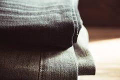 Стог джинсов на деревянной предпосылке, тонизируя винтажное изображение стоковая фотография rf