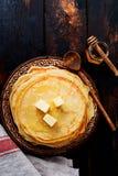 Стог домодельных тонких блинчиков с частями масла, молока и меда на старой деревенской керамической плите стоковые изображения rf