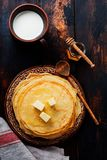 Стог домодельных тонких блинчиков с частями масла, молока и меда на старой деревенской керамической плите стоковые фото