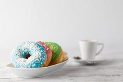 Стог замороженных donuts с кофейной чашкой на таблице Стоковая Фотография RF