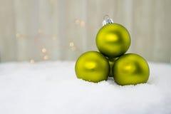 Стог зеленых шариков орнамента на снеге Стоковое фото RF