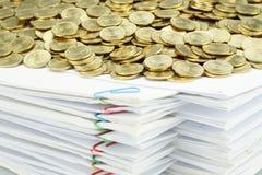 Стог золотых монеток на куче белой обработки документов Стоковое фото RF