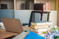 Стог и компьтер-книжка книги на таблице в офисе Стоковое фото RF