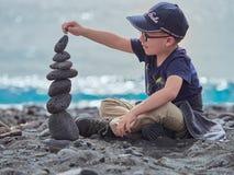 Стог камня здания мальчика на пляже Panarea, Эоловых островов, Сицилии, Италии Стоковые Фотографии RF