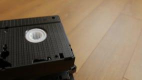Стог кассеты магнитной ленты для видеозаписи VHS над деревянной предпосылкой, взгляд сверху видеоматериал