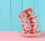 Стог керамических ретро чашек с красными картинами на розовом деревянном столе против голубой деревянной предпосылки стены, тенде стоковые фотографии rf