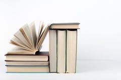 Стог книги, книги hardback красочные на деревянном столе, белой предпосылке задняя школа к Скопируйте космос для текста Образован Стоковое Изображение RF