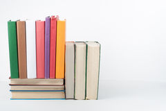Стог книги, книги hardback красочные на деревянном столе, белой предпосылке задняя школа к Скопируйте космос для текста Образован Стоковые Изображения RF