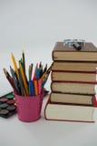 Стог книги, лупа, карандаши цвета и палитра на белой предпосылке Стоковое Изображение RF