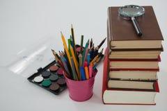Стог книги, лупа, карандаши цвета и палитра на белой предпосылке Стоковое Изображение
