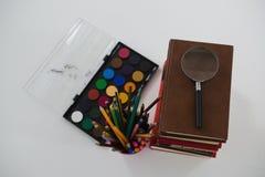 Стог книги, лупа, карандаши цвета и палитра на белой предпосылке Стоковые Фотографии RF