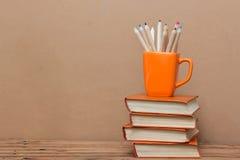 Стог книг и чашки с покрашенными карандашами Стоковая Фотография RF