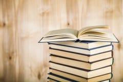 Стог книг на деревянной предпосылке Стоковое Изображение