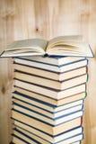 Стог книг на деревянной предпосылке Стоковая Фотография