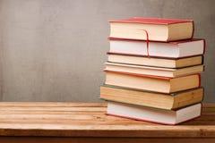 Стог книг на деревянном столе над деревенской предпосылкой Стоковое Изображение