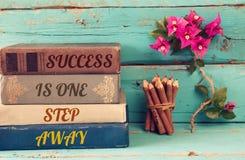 Стог книг над деревянным столом и мотивационной фразой Стоковое фото RF