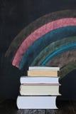 Стог книг с красочной доской в предпосылке Стоковое Изображение RF