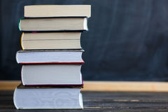 Стог книг с доской в предпосылке Стоковые Изображения RF