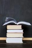 Стог книг с доской школы в предпосылке вертикально Стоковые Фотографии RF