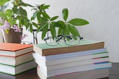 Стог книг с стеклами на деревянном столе Стоковая Фотография