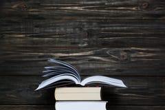 Стог книг с темной деревянной предпосылкой Открытый космос для текста Стоковые Изображения RF