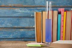 Стог книг, химической пробирки и липких примечаний Стоковое Фото