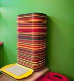 Стог красных, желтых, зеленых подносов на таблице стоковые фото