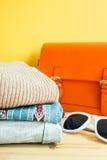 Стог красочных одежд и оранжевой сумки, солнечных очков на таблице Стоковое Изображение