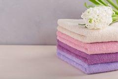 Стог красочных полотенец ванны с цветком гиацинта на задней части света Стоковое фото RF